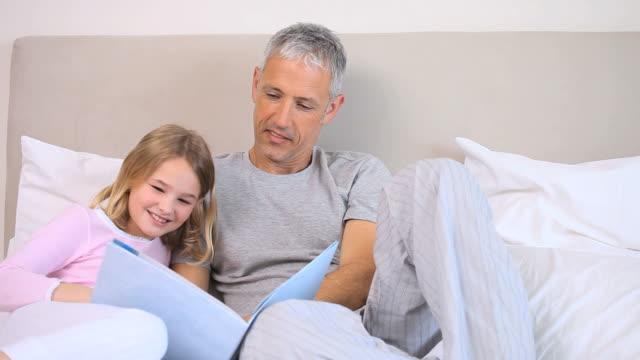 vídeos de stock e filmes b-roll de father and daughter reading a book - cabelo branco
