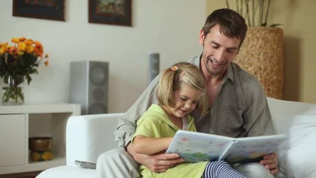 vídeos y material grabado en eventos de stock de ms father and daughter (4-5) reading book on couch / potsdam, brandenburg, germany - en el regazo