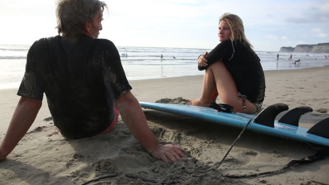 Father and daughter relax on beach after surfing