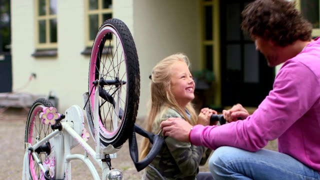 stockvideo's en b-roll-footage met father and daughter repairing bicycle tire - genderblend