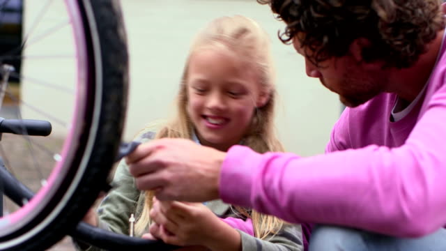 father and daughter repairing bicycle tire - genderblend stock videos & royalty-free footage