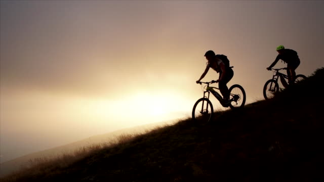 父と娘の夕日で山の頂上にマウンテン バイクに乗る - マウンテンバイキング点の映像素材/bロール