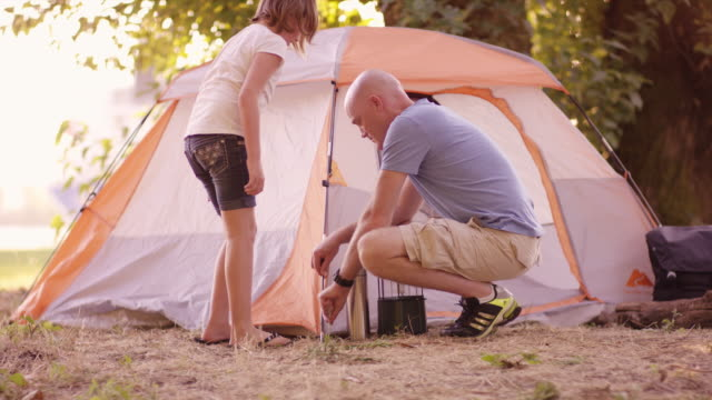 Father and daughter setting up a tent together outdoors