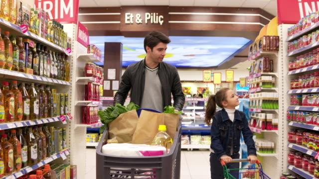 vater und tochter in einem supermarkt einkaufen - alleinerzieher stock-videos und b-roll-filmmaterial