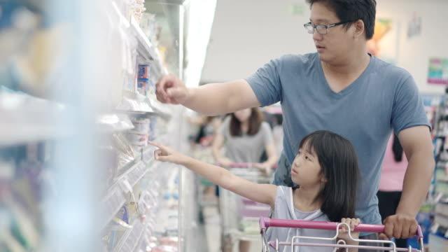vater und tochter in ein supermarket.4k einkaufen - einkaufswagen stock-videos und b-roll-filmmaterial