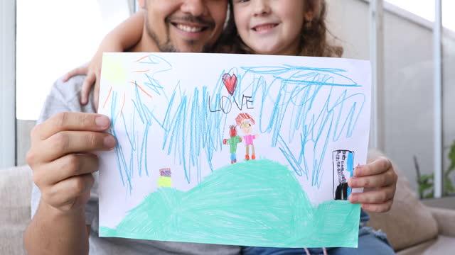 父の日のために彼を作ったカードを見せる父と娘 - dia点の映像素材/bロール