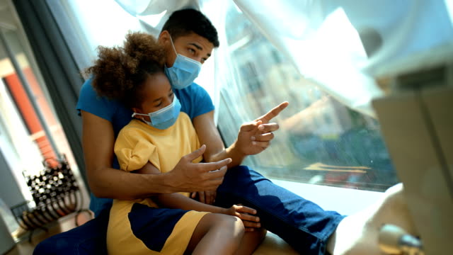 father and daughter sitting by a window during coronavirus quarantine. - side view stock videos & royalty-free footage