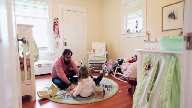 WS Father and daughter sitting in daughters bedroom father helping daughter with dolls shoes/Seattle, Washington, USA