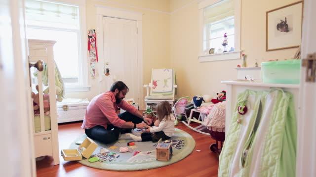 vídeos y material grabado en eventos de stock de ws father and daughter sitting in daughters bedroom father helping daughter with dolls shoes/seattle, washington, usa - genderblend