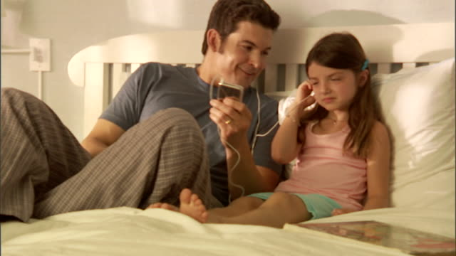 MS, Father and daughter (6-7) sitting on bed, listening MP3 player