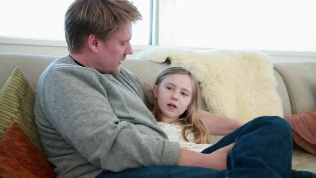 Father and daughter sitting on sofa talking