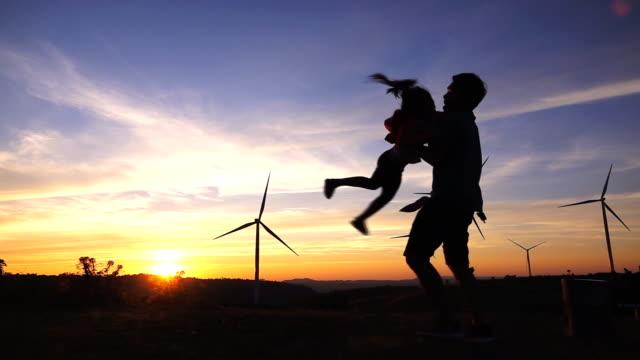 slo-mo-vater und tochter, die spinnerei in turbinen windpark bei sonnenuntergang - fuel and power generation stock-videos und b-roll-filmmaterial