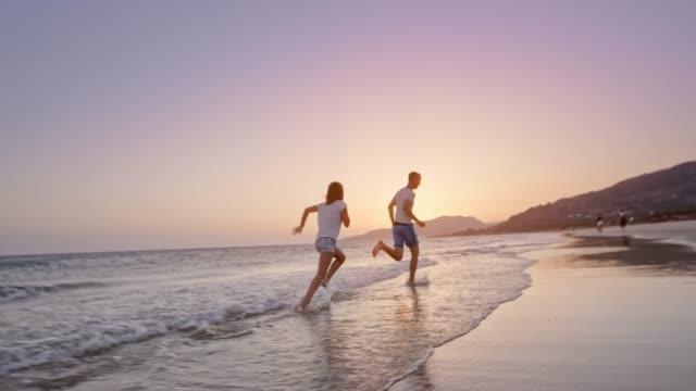 SLO MO padre e hija salpicaduras de agua el uno al otro en la playa en el atardecer y el funcionamiento