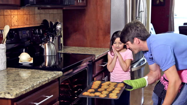 father and daughter take cookies out of oven - stereotypical homemaker stock videos & royalty-free footage