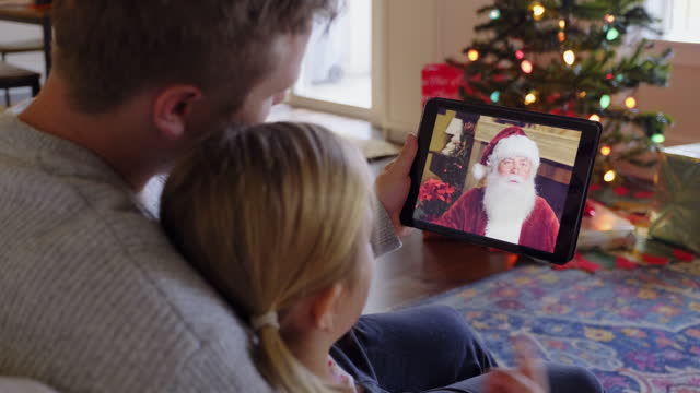 Father and Daughter Talking to Santa Claus on a Video Call