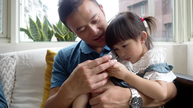 father and daughter using a mobile phone together sitting on the sofa at home - holding stock videos & royalty-free footage