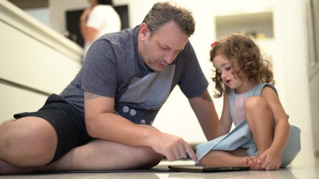 father and daughter using digital tablet at home - fathers day stock videos & royalty-free footage