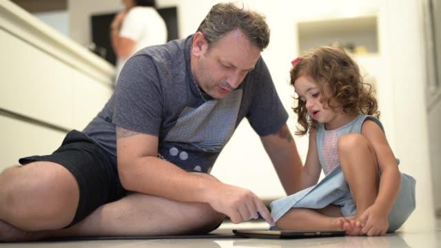 vídeos de stock, filmes e b-roll de pai e filha que usam a tabuleta digital em casa - etnia caucasiana