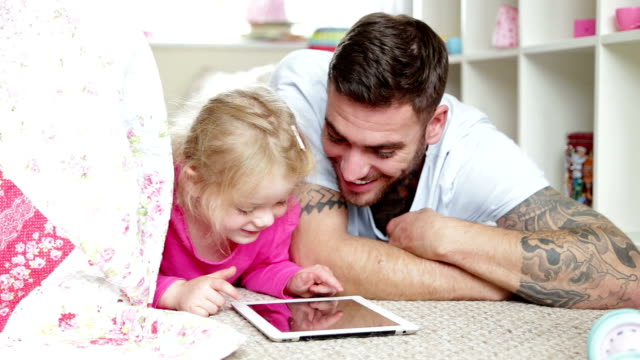 father and daughter using digital tablet - lying on front stock videos & royalty-free footage