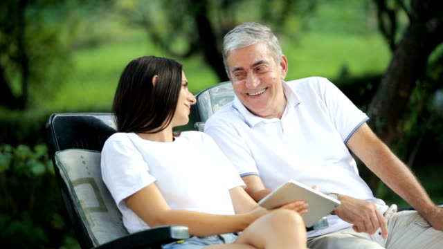 Father and daughter using tablet and talking