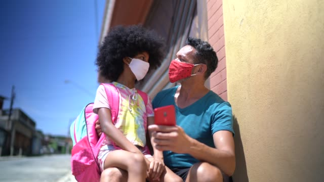 father and daughter waiting for school bus and using mobile phone in front of house - with face mask - commercial land vehicle stock videos & royalty-free footage