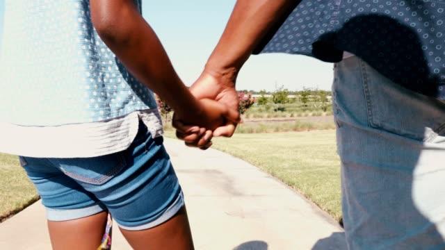 vídeos y material grabado en eventos de stock de padre e hija caminan de la mano en un parque en un día de verano - intergénero