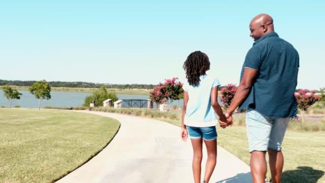 vídeos y material grabado en eventos de stock de padre e hija caminan por el camino juntos cerca del lago - intergénero