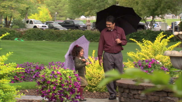 MS DS Father and daughter (6-7) walking around fountain carrying umbrellas / Heber City, Utah, USA