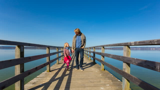 MS Father and daughter walking on pier