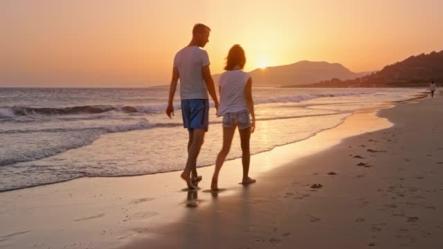 vidéos et rushes de père et fille marcher sur la plage de sable et de parler comme le soleil se couche - jeunes filles