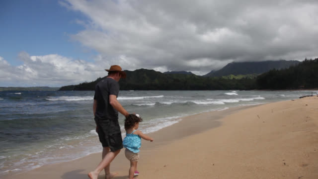 father and daughter walking up a tropical beach playing in the waves - プエルトリコ人点の映像素材/bロール