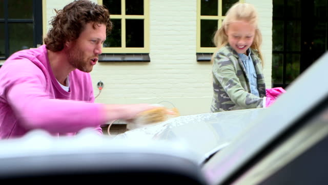 stockvideo's en b-roll-footage met father and daughter washing car - genderblend