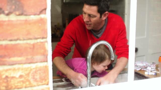 vídeos de stock e filmes b-roll de father and daughter washing utensils - fazer um favor