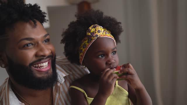 vídeos de stock, filmes e b-roll de pai e filha assistindo tv e comendo watermolon em casa - fruta