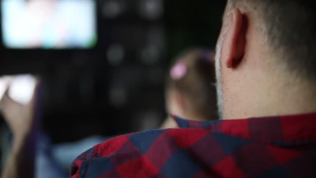vidéos et rushes de père et fille regardant la télévision ensemble - jouet
