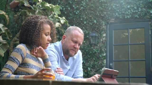 ms td father and daughter watching video on digital tablet in backyard - single father stock videos & royalty-free footage