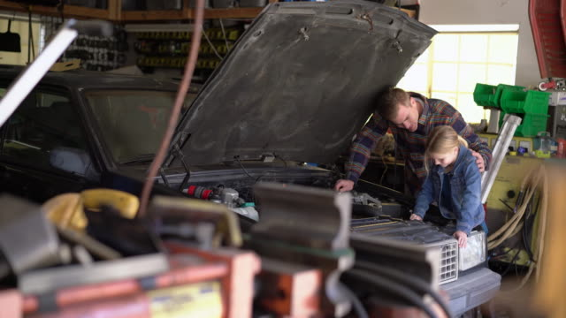 WS Father and daughter working on a car's engine together