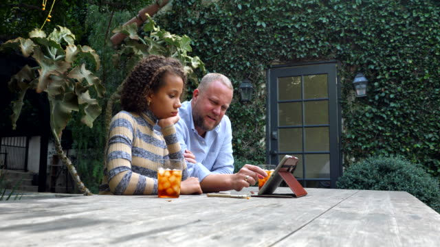 ms father and daughter working on digital tablet together in backyard - single father stock videos & royalty-free footage