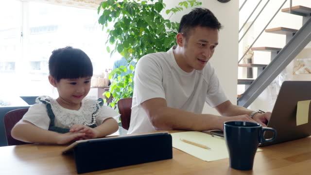 vidéos et rushes de père et descendant travaillant ensemble à la maison - working girl
