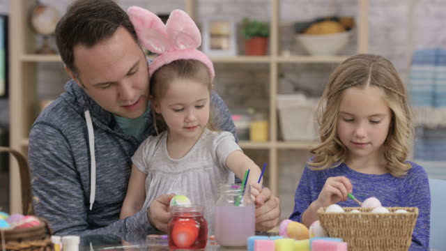 Father and Daughters Painting Easter Eggs