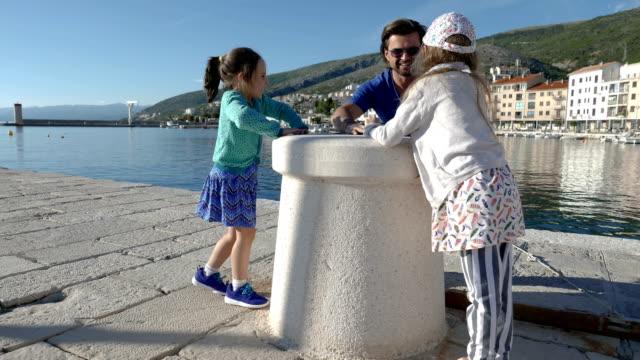 Vater und Töchter spielen auf einem pier