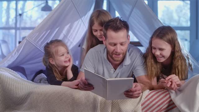 vídeos y material grabado en eventos de stock de padre e hijas pasando tiempo juntos en una acogedora cama con dosel. libro de lectura - monoparental