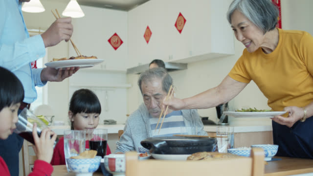 father and grandmother serving food to family at chinese new year - chinese new year stock videos & royalty-free footage