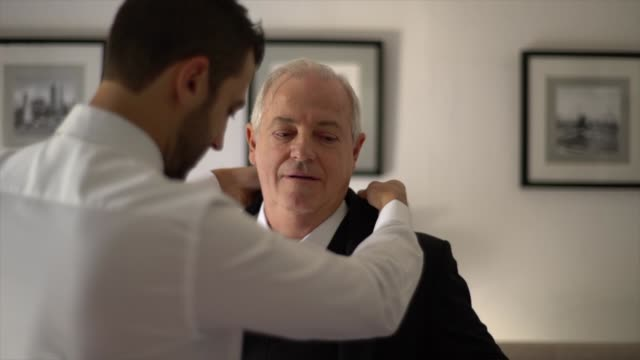 father and groom getting dressed for the wedding - life events stock videos & royalty-free footage