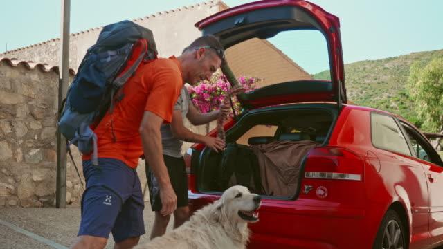 vidéos et rushes de père et son fils adulte chargement voiture pour un week-end de randonnée avec leur chien - golden retriever