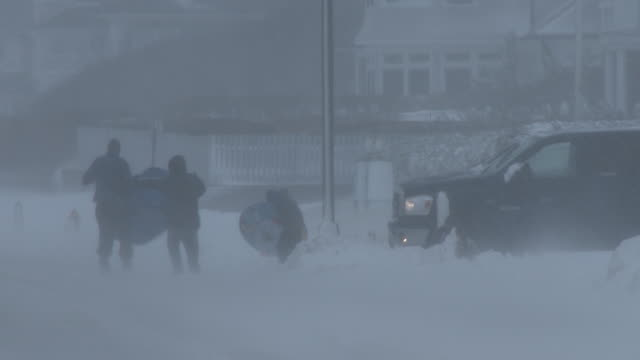 father and his children can barely stay on their feet, as they struggle with a snow tube in near whiteout conditions and very strong winds on the... - struggle stock videos & royalty-free footage