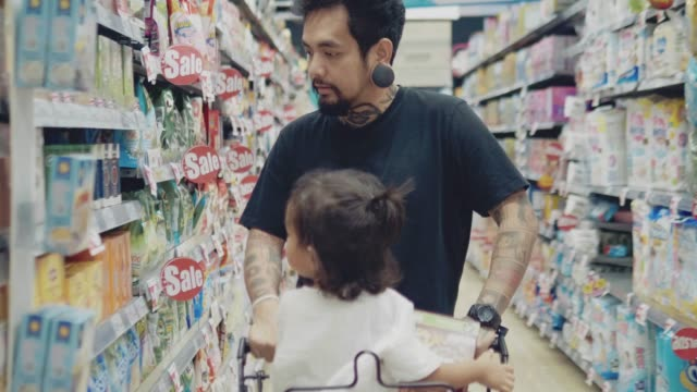 father and his little baby in the supermarket. the child sits in the cart and looks at his father with delight. a man is talking to him. father's day - aisle stock videos & royalty-free footage