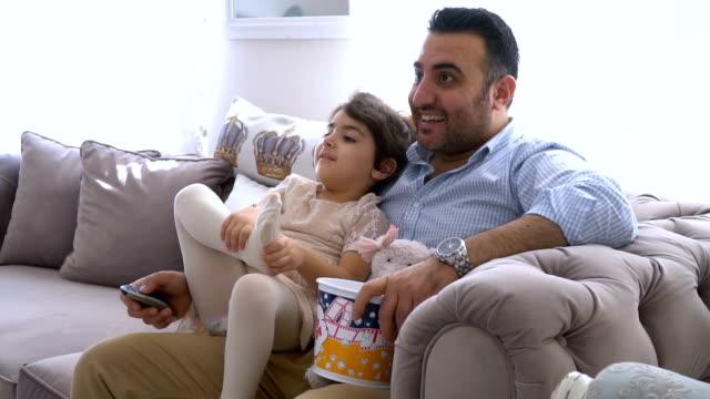 vídeos y material grabado en eventos de stock de un padre y su hija pequeña sentados en el sofá y comiendo palomitas de maíz mientras miran la televisión - father day