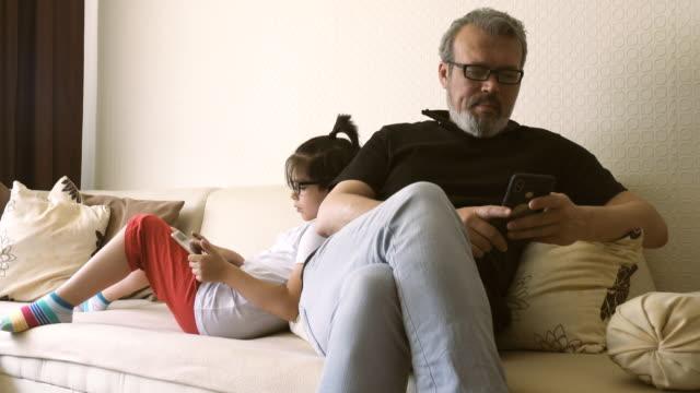 vidéos et rushes de père et son fils se phubbing à la maison - photo messaging