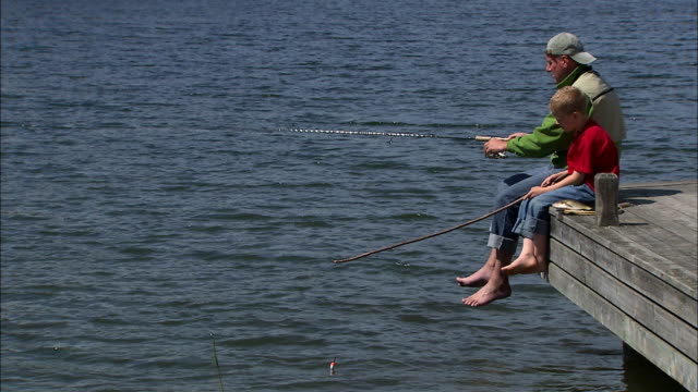 vidéos et rushes de a father and his son sitting on a jetty fishing sweden. - casquette de baseball